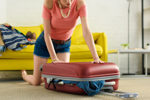 girl packing suitcase for trip